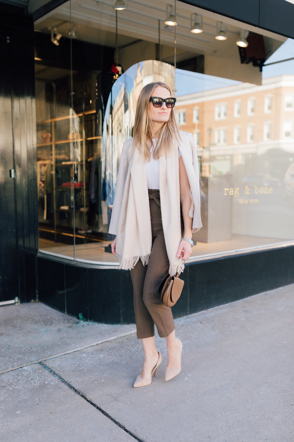 Stephanie Trotta of The Girl Guide wearing a paper bag pant street style for work wear with a neutral blazer and scarf and wearing Celine sunglasses