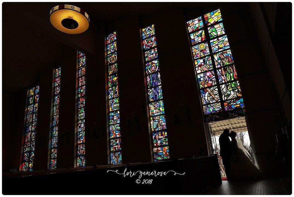 brideandgroomposingbybeautifulstainedglasswindowsinchurchlgphotography.jpg
