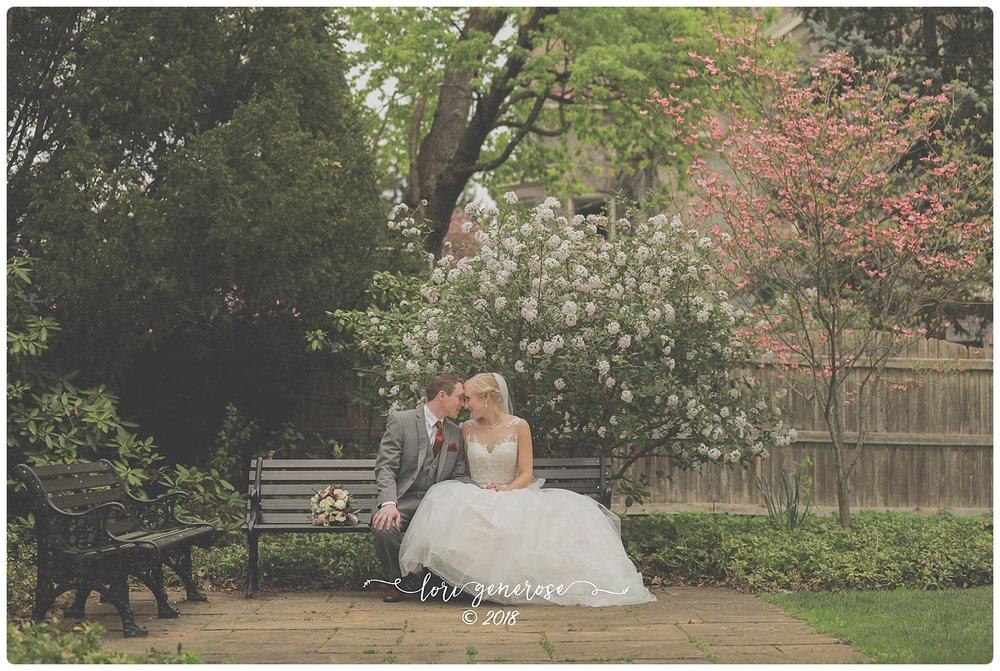 lgphotographylorigenerosetheinnatpoconomanorpaweddingvenuebridegroomsittingonbenchfloweringtrees.jpg