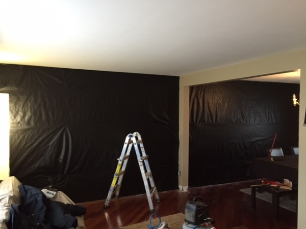 Step #1  Cut and staple tar paper to the wall. The black background makes and holes/cracks in the barn board disappear on the wall.