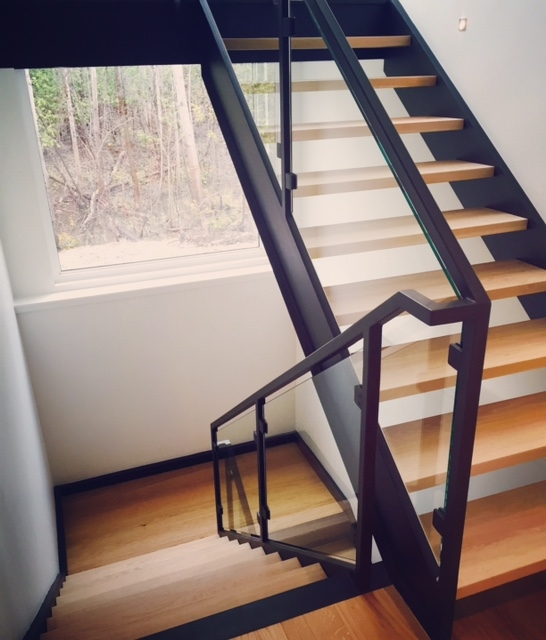 Tubular steel railing with custom glass slips - custom painted black.  10mm clear tempered glass was installed in this system.  Job location: Blue Mountain, ON