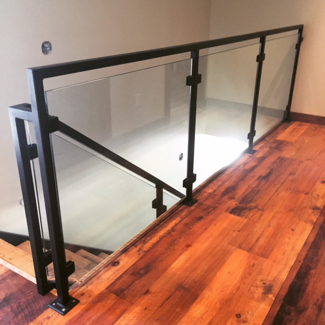 Tubular steel railing (painted black) with 10mm clear tempered glass (glass clip system).  Job location: Blue Mountain, ON