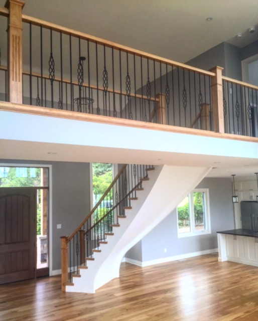 Stairs and railings supplied & installed by Stairhaus. Open 2 sides circular stair with full heels - paint grade stringers and risers/hickory treads. Oversized standard hickory railing with 4-1/2 fluted posts & TL15-40/TL103-1-40 wrinkled black spindles.  Job location: Blue Mountain, ON.