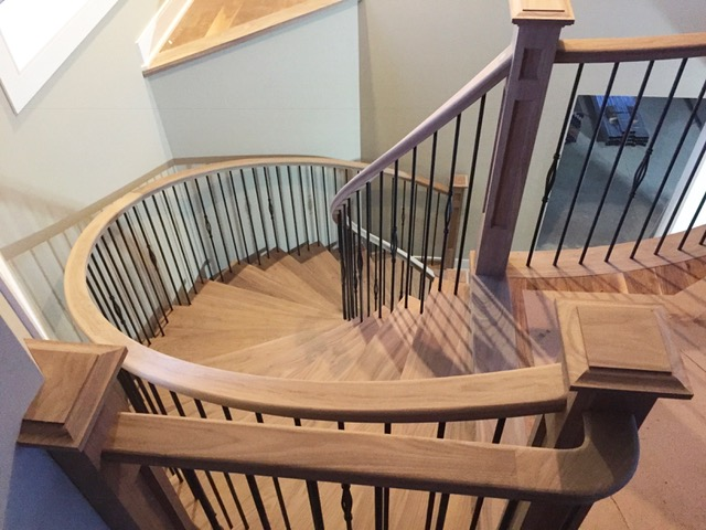 This open 2 sides, open rise circular was dressed up with our standard rail, 4-1/2 double square shaker posts with TL15-40 & TL102-1RD-40 wrinkled black spindles. Walnut rules!  Job location: Essa, ON.