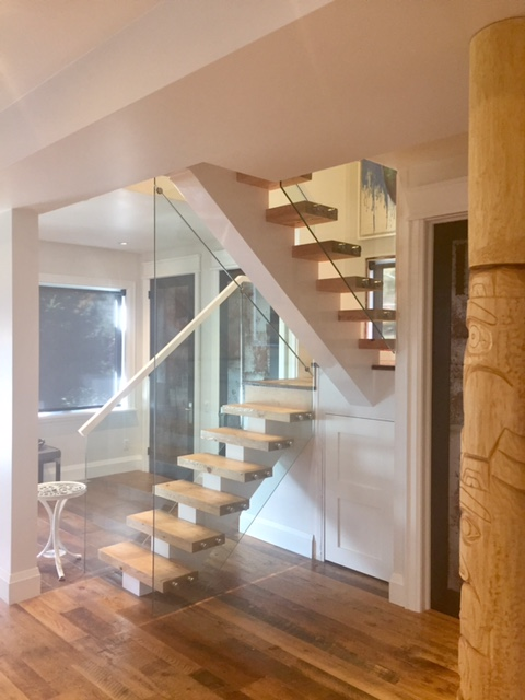 "his stair has a wood mono-stringer with 2-3/4"" reclaimed hemlock treads. We used 12mm clear tempered glass with 1-1/2"" stainless steel standoff's.  Job location: Barrie, ON."