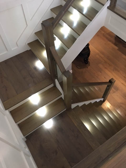 Stairs and railings supplied & installed by Stairhaus. These stairs have 1-1/16 white oak treads, paint grade risers and stringers with hidden Liteline low profile LED stair lights. We installed 4-1/2 white oak plain posts with a flat 2x4 railing. The glass was installed using 12mm stainless glass clips. Job location: Barrie, ON.