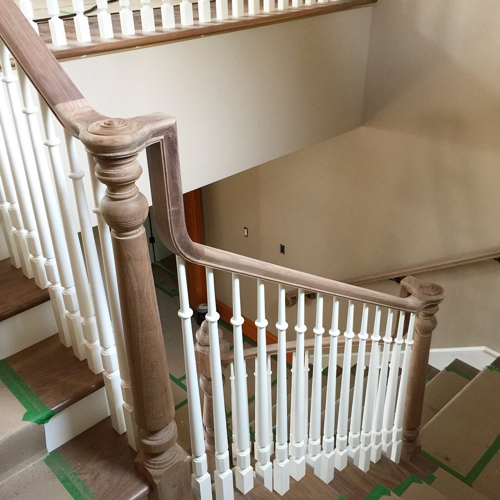 Custom tuned walnut volute posts with custom dowel top paint grade spindles.  Job location: Barrie, ON