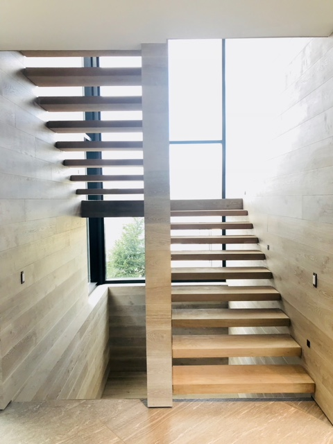 "Infinity white oak stairs with 3"" box treads.  The treads are supported by hidden steel brackets in the walls.  Job location: Muskoka, ON"
