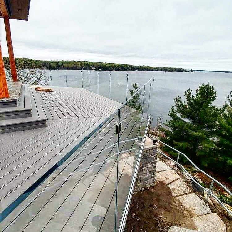 12mm clear tempered glass installed using a hidden fascia mounted base shoe.  Job location: Muskoka, ON.