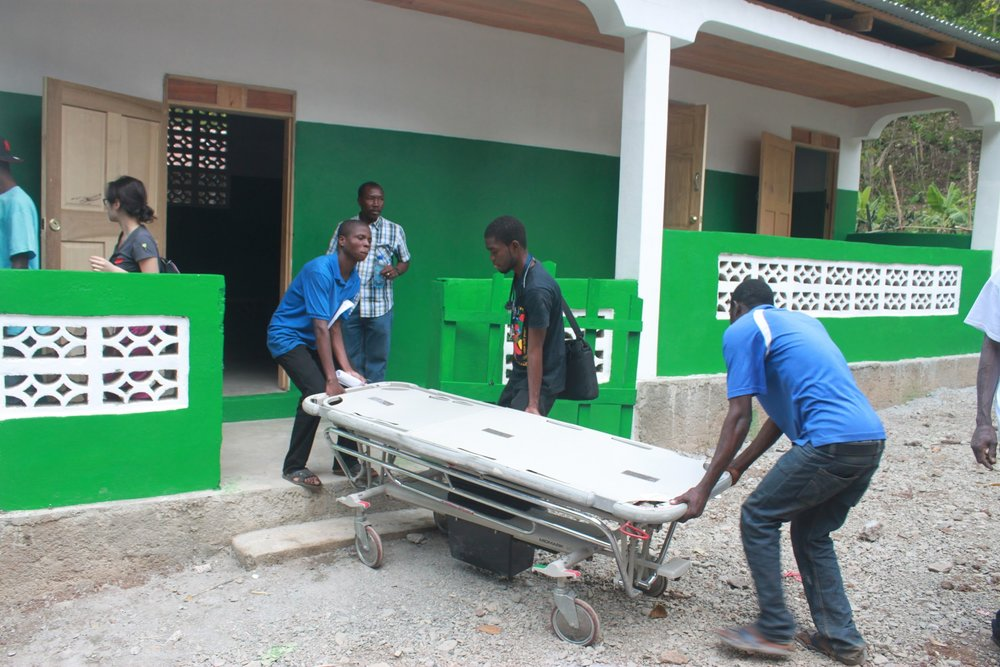 Dr. Gueslin Jossainvil and colleagues bring a gurney into the Chermaitre-Fiervil medical clinic funded by VHP.