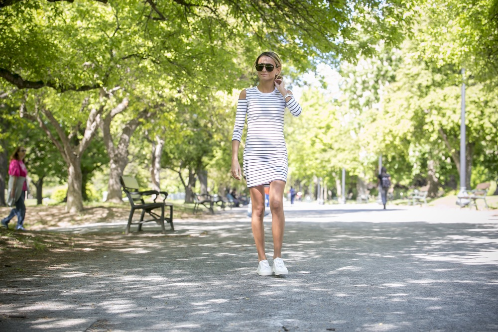 Lauren Recchia from the fashion blog North of Manhattan wearing a french connection striped dress with cold shoulders and white leather sneakers for spring streetstyle