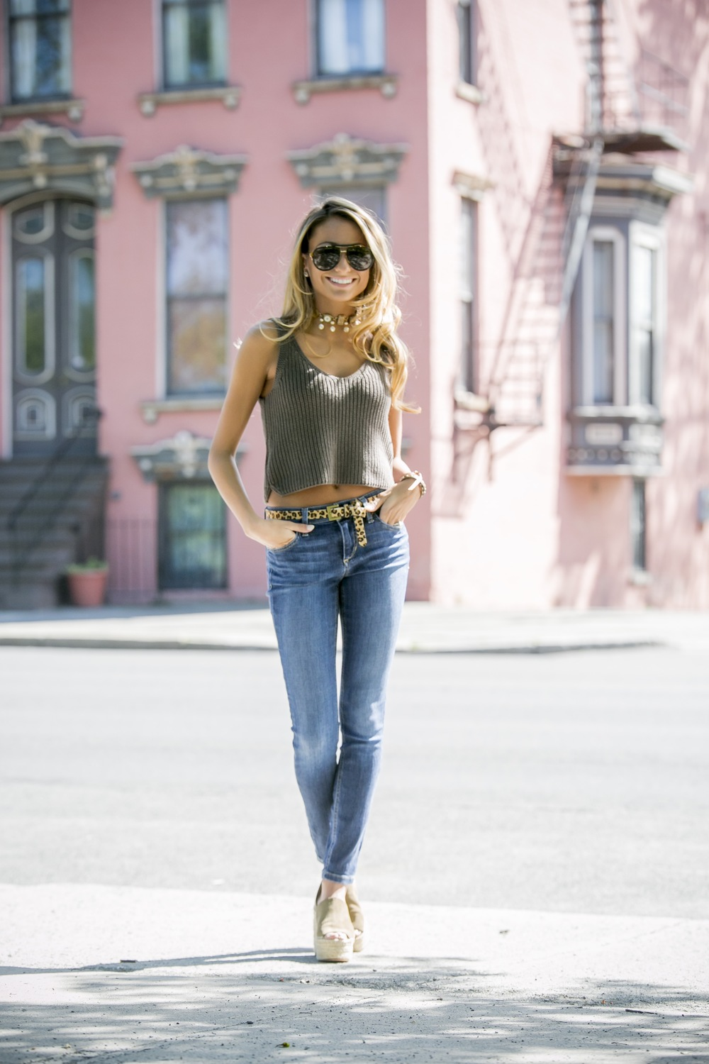 fashion blogger Lauren Recchia from North of Manhattan seen in a knit crop top, calf hair belt, Joe's Jeans, and Olive chloe wedges