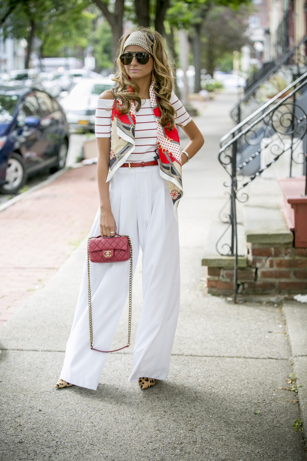 Streetstyle fashion blogger Lauren Recchia seen in Alice and Olivia wide leg trousers with an off of the shoulders sweater and head scarf