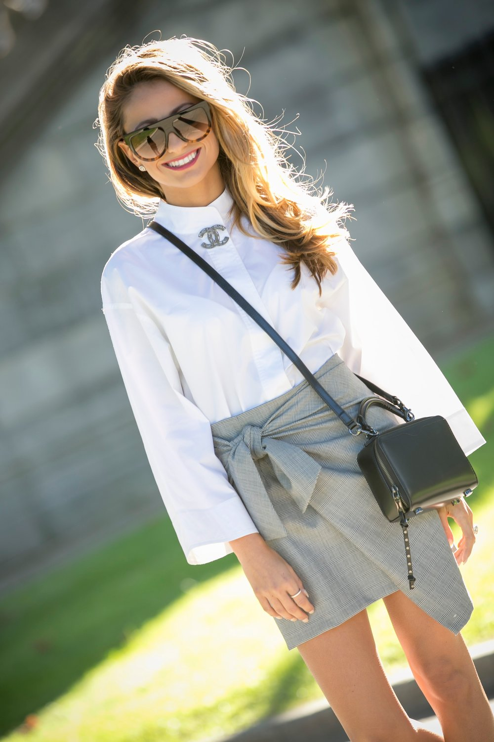 fashion blogger streetstyle in a white blouse and knot skirt