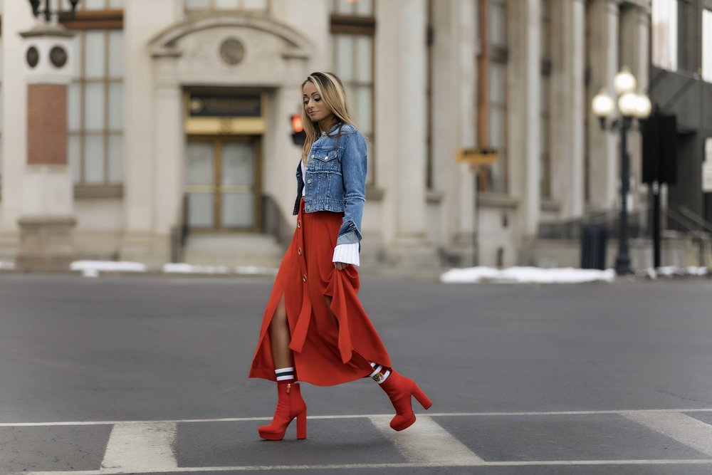 streetstyle in a cropped denim jacket, belted midi skirt, and prada boots