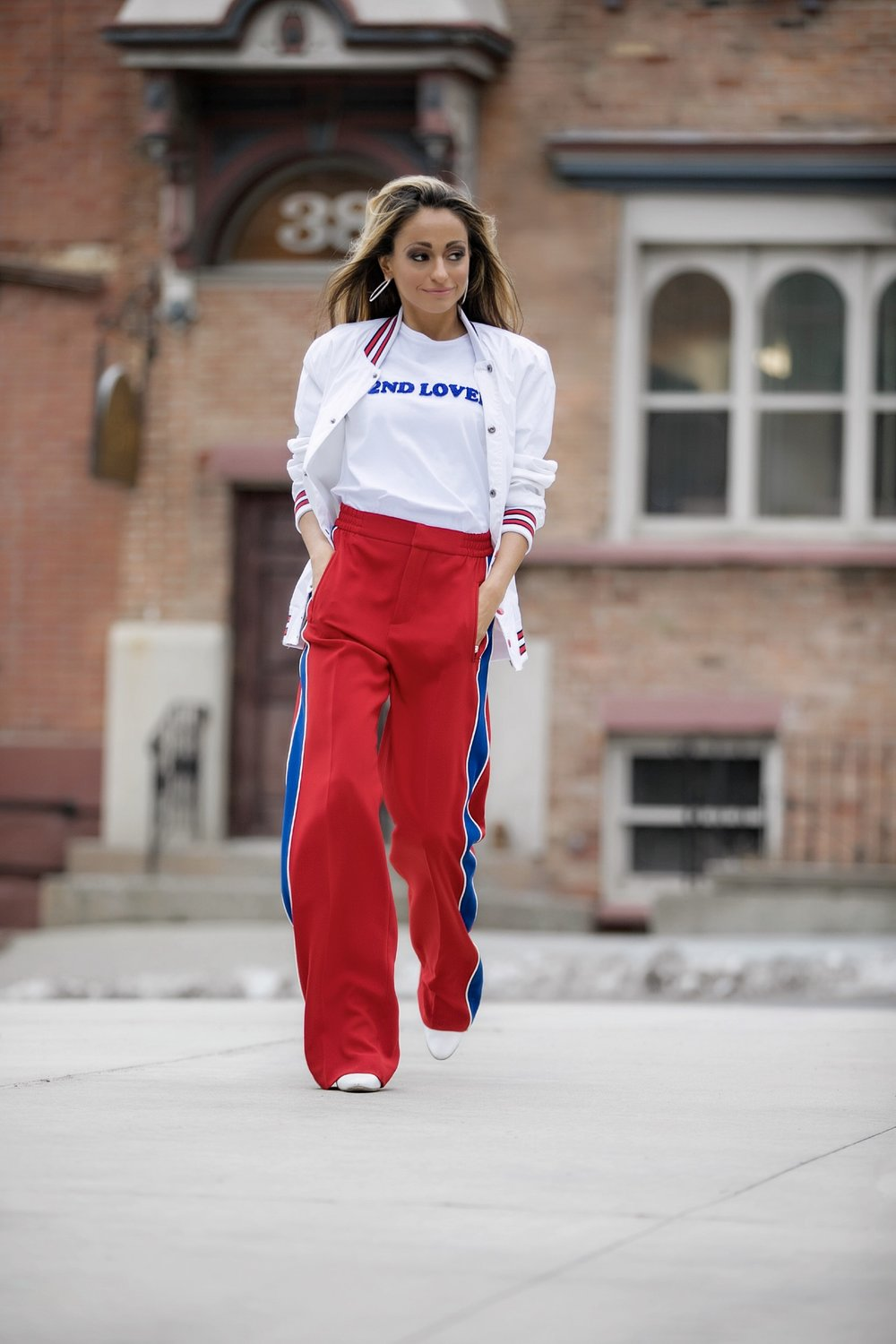 graphic tee, sporty style track pants, and Manolo Blahnik boots