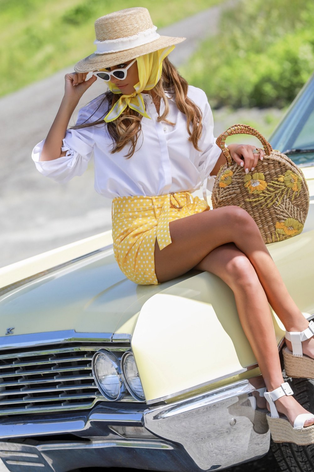 retro inspired look in polka dot shorts, thick white cat eye sunglasses, and a straw bag