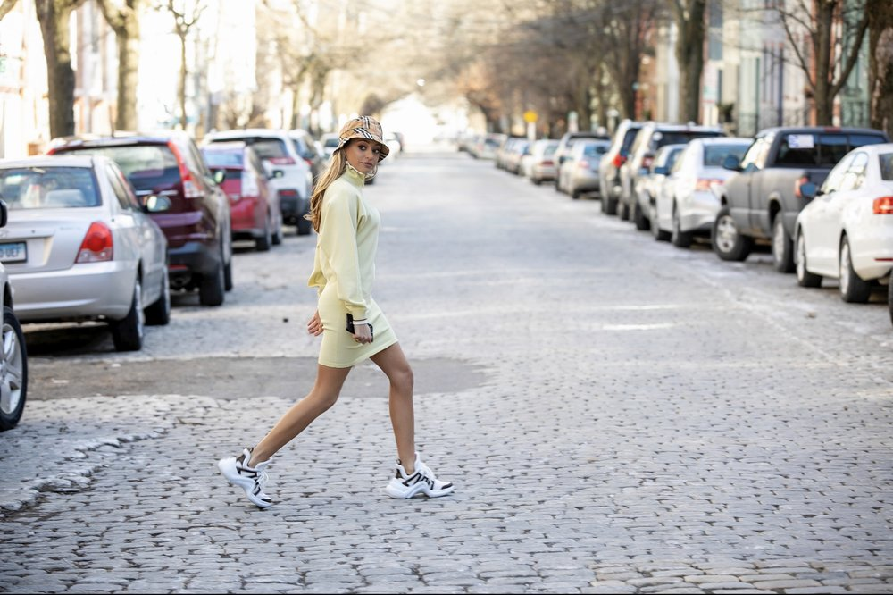 New York City streetstyle blogger in a Burberry bucket hat, Isabel Marant Etoile knit dress, and Louis Vuitton sneakers