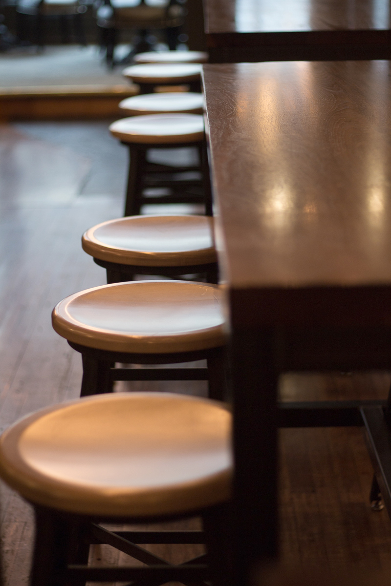Custom stools and walnut table at Pressroom restaurant