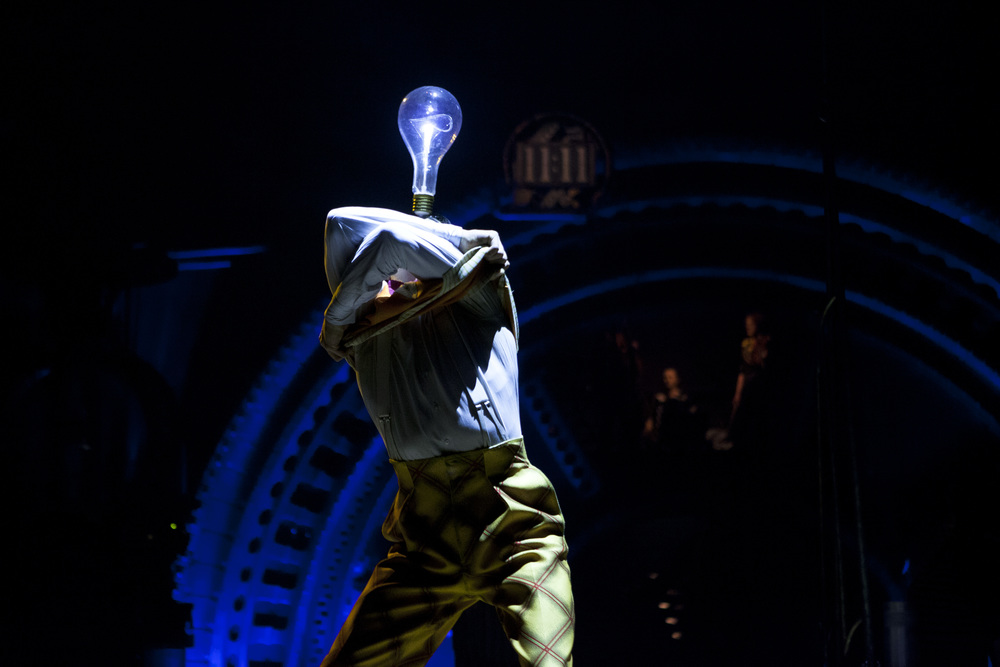 A Cirque du Soleil performer balances a light bulb on his head while adjusting his costume in Marymoor Park, Redmond on Thursday, Jan. 29, 2015.