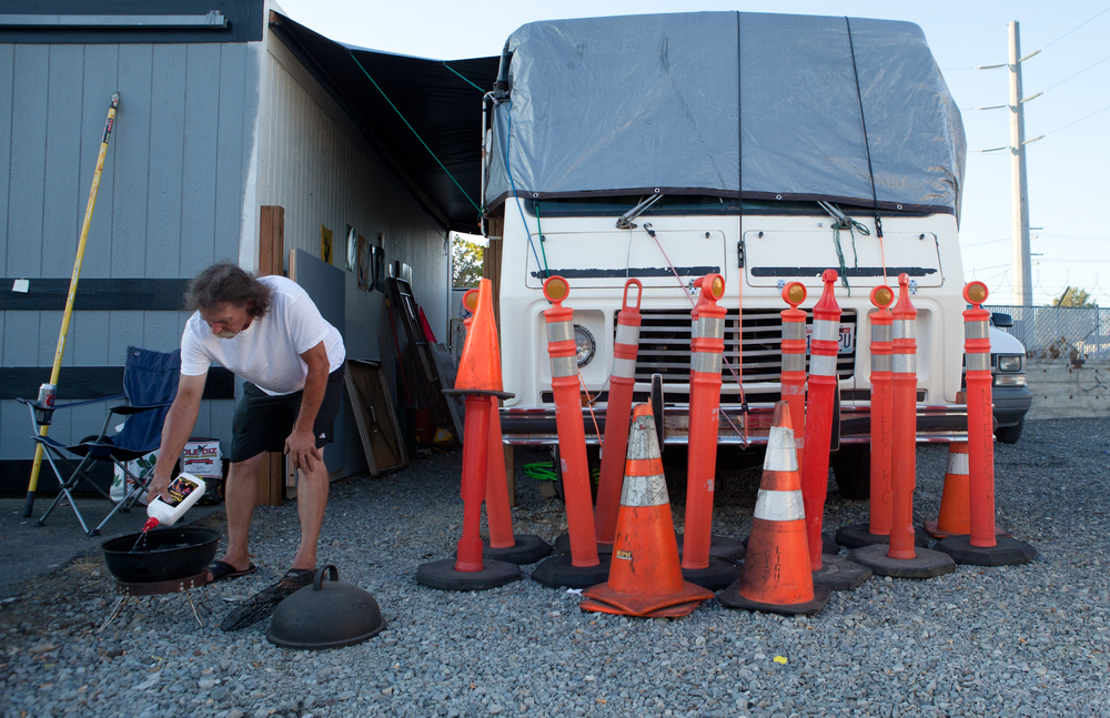 Bud Dodson, 57, prepares for a BBQ dinner in a South Seattle vacant lot where he makes his home -August, 2014.