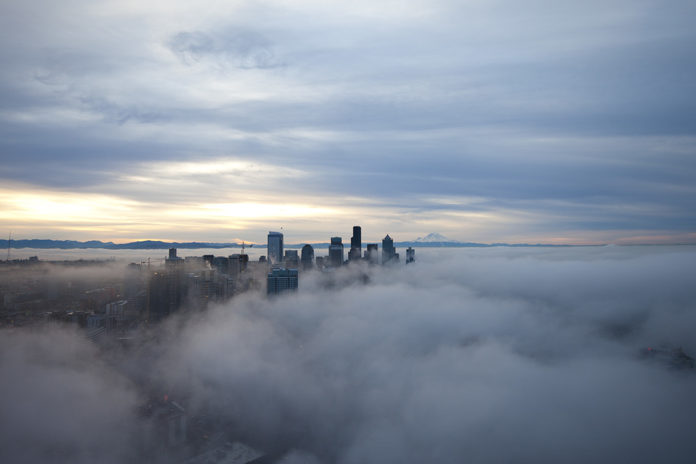 View from atop of the Space Needle as fog rolls in Downtown Seattle in the early morning in January 2015.