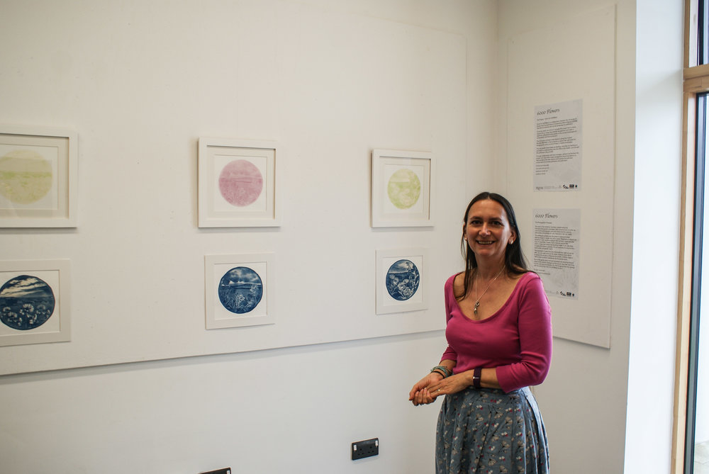 Artist Josie Purcell alongside some of her work for 6000 Flowers