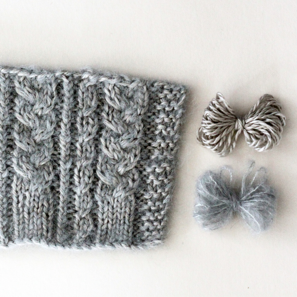 Cabled swatch knitted with one end of Scrumptious 4ply in #318/Glisten (top yarn butterfly) and one end of Cumulus  in #911/Silver (bottom yarn butterfly)