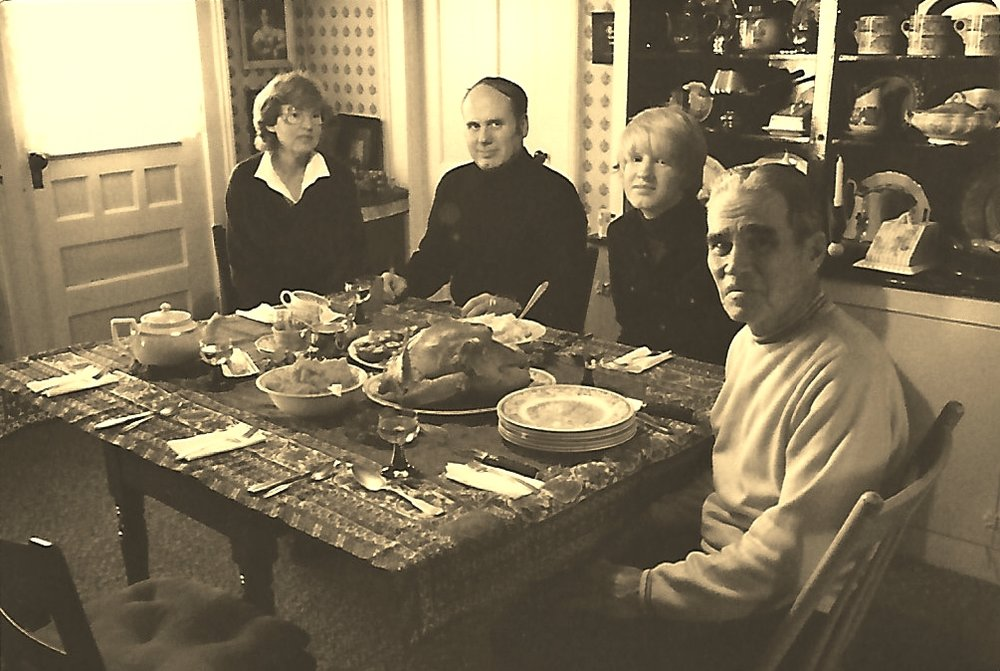from right to left: My grandfather French, my brother, father and mother with Thanksgiving meal on the table.