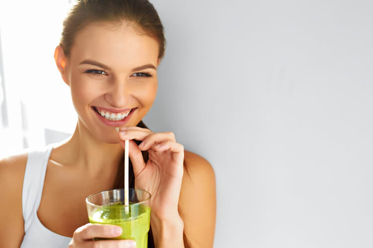 happy woman drinking green smoothie.jpg