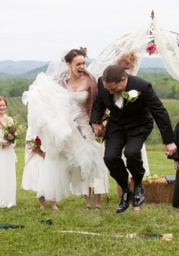 action shot bride and groom jump