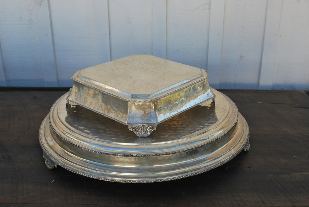"""Silver Cake Stands $15 each, 3 available. The largest is 22"""" on the top and 27"""" across bottom. The other is 12"""" across the top and 15 1/2"""" across the bottom. One more available - see picture."""