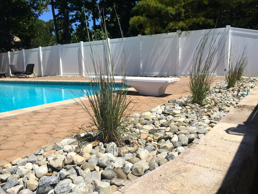 Ornamental Grass w/ river rock by the pool Design by jason t.