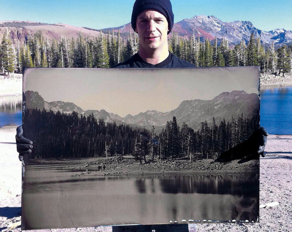 Ian Ruhter holding one of his earlier wet plate prints from Yosemite National Park