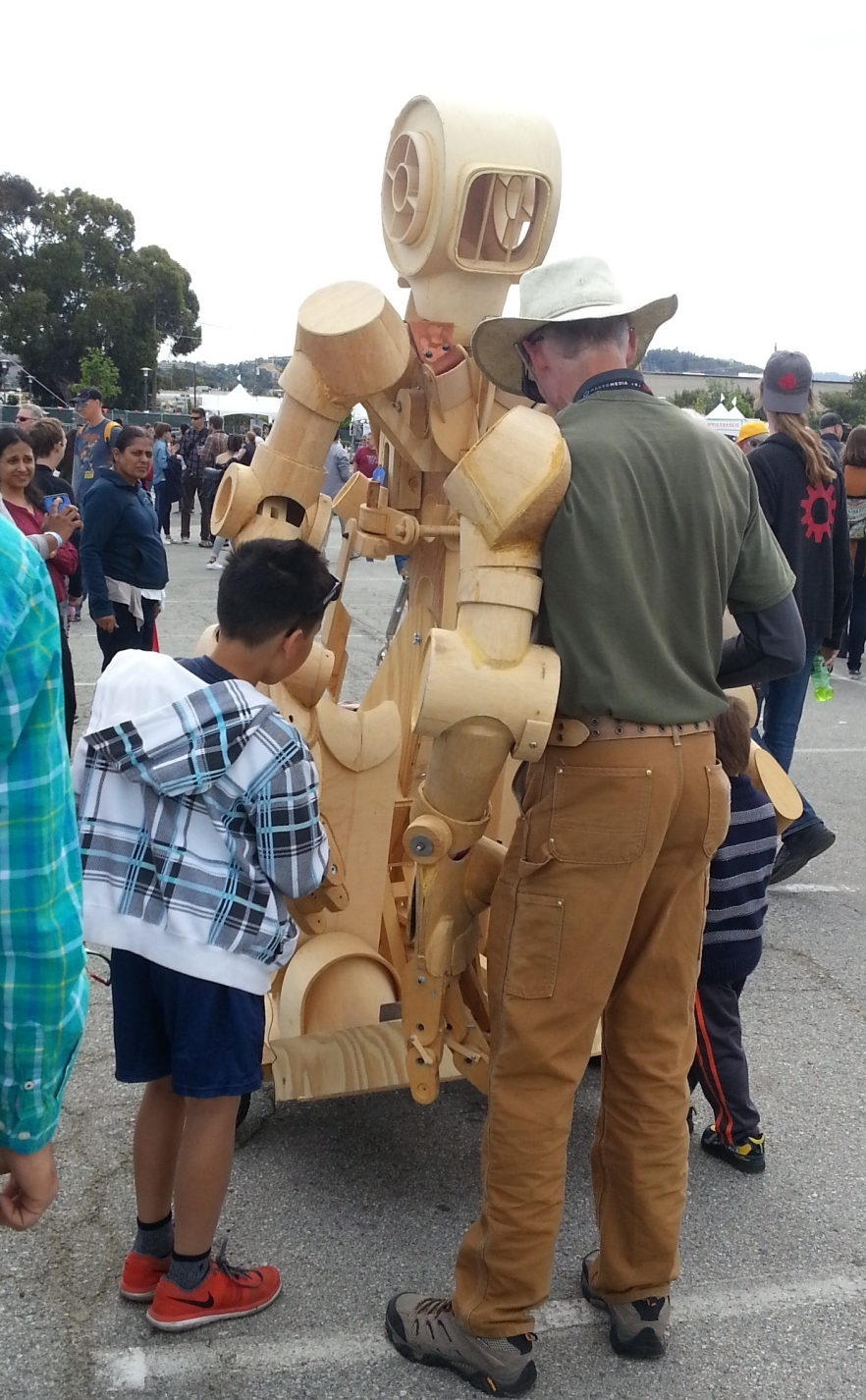 This guy is showing some kids the finer points of his fully articulated wooden robot suit.