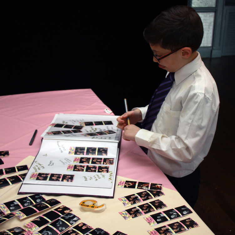 child signing photo scrapbook