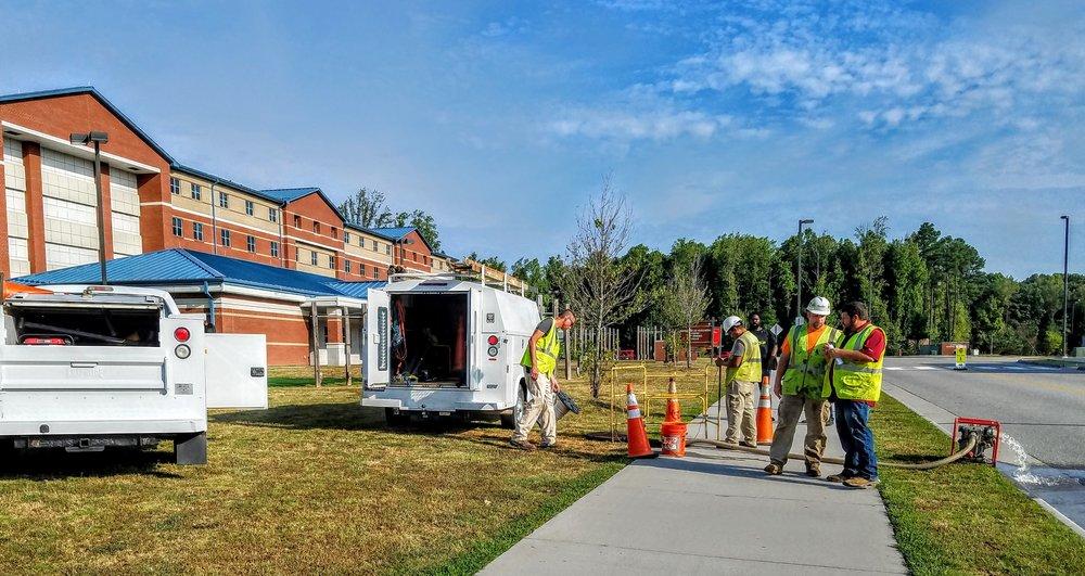 Crews prepare to enter a manhole to place fiber optic cable to Army barracks