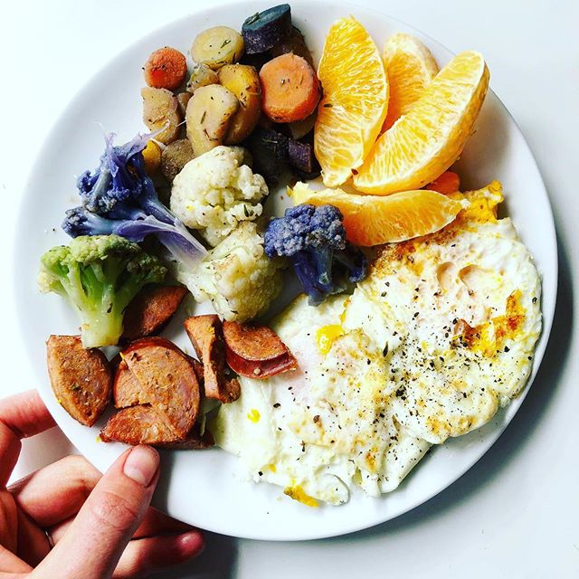 Breakfast happened at 11AM today. 🤷🏼‍♀️ after spin class, a trip to 🎯, and a few errands, I was starving and highly caffeinated (thanks, cup of coffee #2). # I made this in 10 minutes in two pans: diced turkey kielbasa and fried eggs in @fourthandheart ghee in one pan, and frozen cauliflower medley and carrot medley (both frozen items from @traderjoes 🙌🏻) in another pan. Baby woke up from her nap as soon as I plated it. Eating while nursing is standard M.O., plus she has the opportunity to enjoy the crumbs. 😋