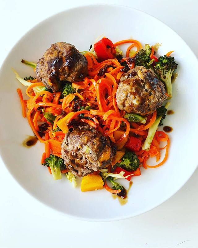 Keeping it colorful tonight // sweet potato-y meatballs with spiralized carrots (from @traderjoes — I've never spiralized anything. ever. ) drizzled with a teriyaki sauce. Adding the sweet potato to the meatballs changes the texture to be a bit more soft, and less meaty. Which, is saying a lot for a MEATball.  The meatballs: 1 lb ground beef, 1 cup mashed sweet potato (I just microwaved it), 1/2 onion diced, 1 egg, 1/4 cup almond flour, garlic powder, 21 seasoning salute (a la TJs, but a similar spice blend will do) and S&P for 400 degrees for 25 minutes.  Theres a million ways to make a teriyaki sauce, here how I did it tonight: 1/2 cup of coconut aminos, 1 tsp sesame oil, 1 heaping tbsp honey, 1/4 tsp ginger powder, 1 tsp garlic powder. Whisk, and cook over medium, until its thick and saucy.