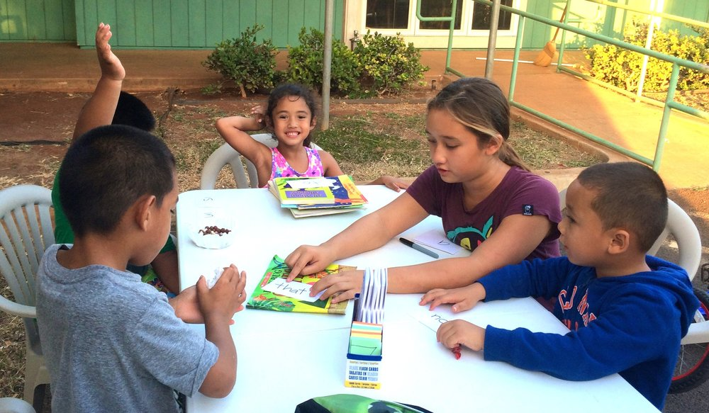 A peer tutor (Alaka'i) works on sight words with her student (Kamali'i). Each Alaka'i is provided with a toolkit of resources to use with their Kamali'i, including flash cards, books, literacy activities, and assessment materials.