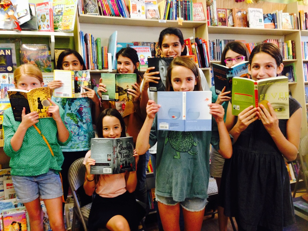 The girls grab their favorite books from the shelves at One More Page bookstore.