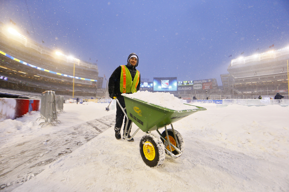 A stadium series worker transports snow away from the ice rink.jpg