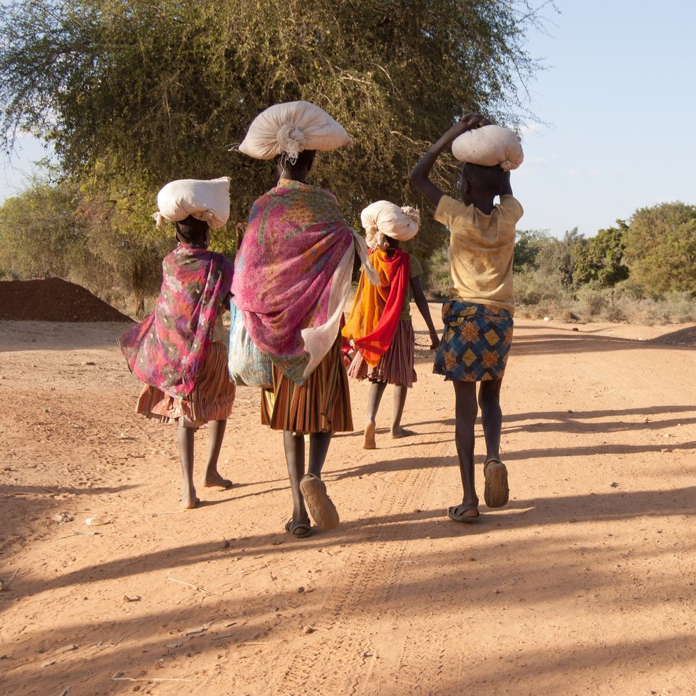 Women walking in village with bags on their heads.jpg