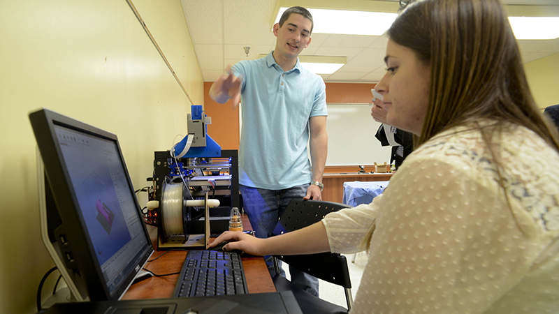 Feature Photo: Joseph Sinclair of Shillington, an adjunct faculty member at Penn State Berks and owner of Solid Dynamics L.L.C., talks about 3-D printing while sophomore Brianna Kondos operates one of the printers during the opening of the Langan LaunchBox.    Image: Bill Uhrich, Reading Eagle