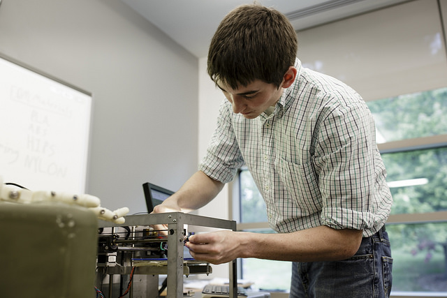 Joseph Sinclair feeds in the plastic material required for this 3D-Printer to operate and produce components.