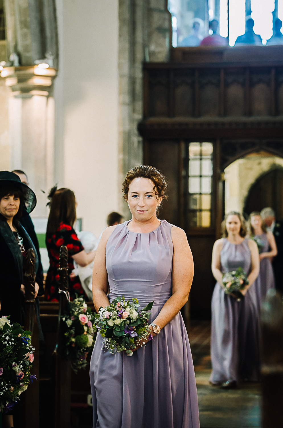 Bridesmaid Walking Down the Aisle at Cottenham All Saint's Church - Swynford Manor Wedding Photographer