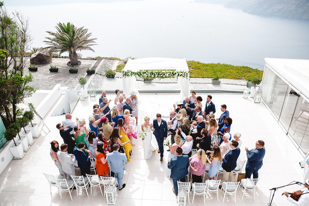 CONFETTI AFTER THE OUTDOOR WEDDING CEREMONY IN SANTORINI GREECE