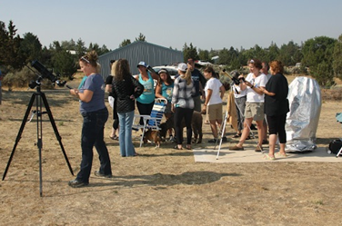 Folks age 5 to 87 gathered in chairs and on the observing field with 5, solar-filtered telescopes.