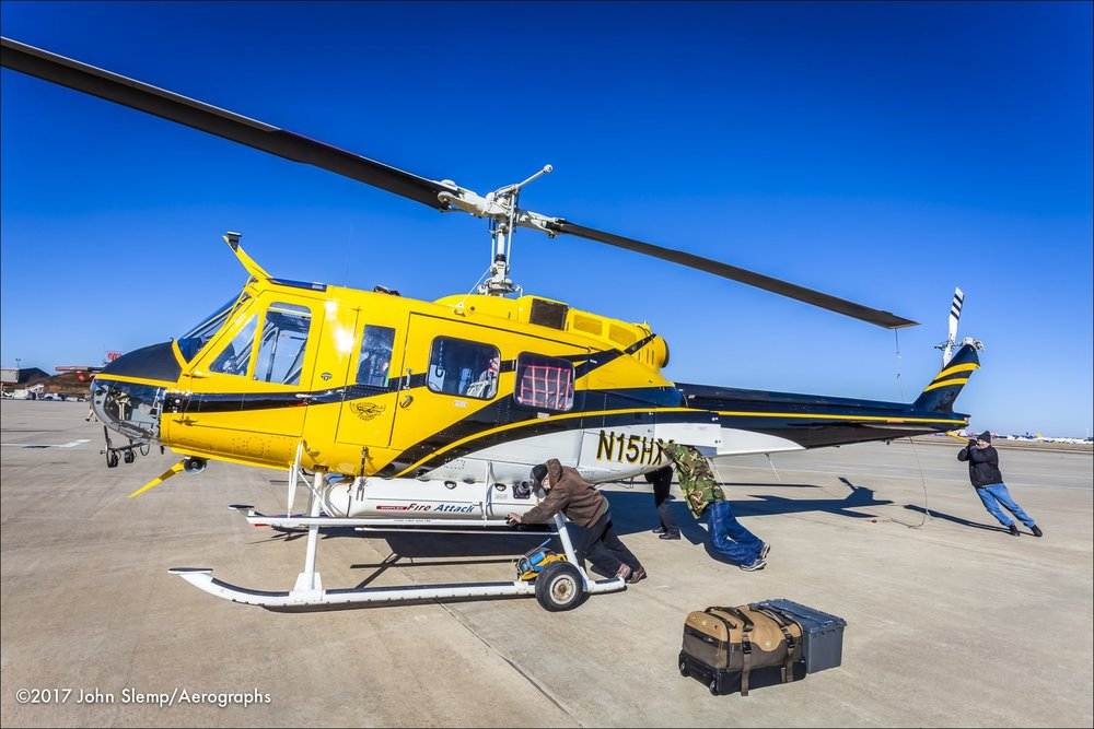 Helicopter Express crewmen push a Bell 205 A-1 into position for cargo flight preparation.