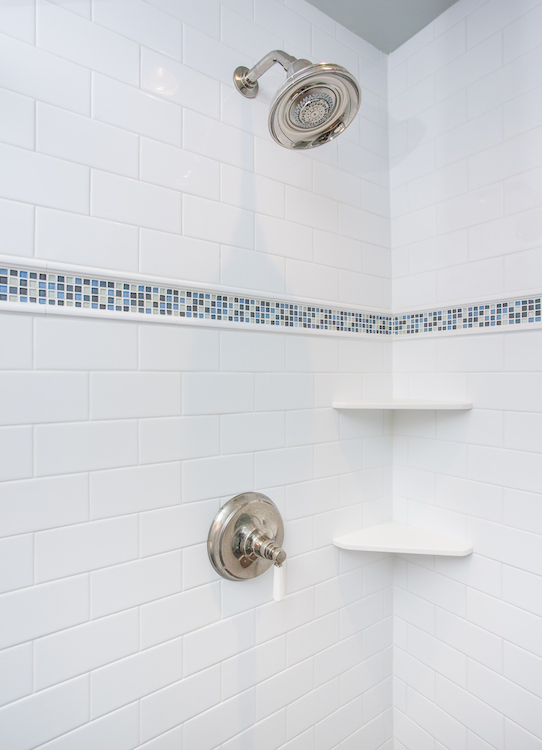 Shower with white subway tile and square mosaic tile